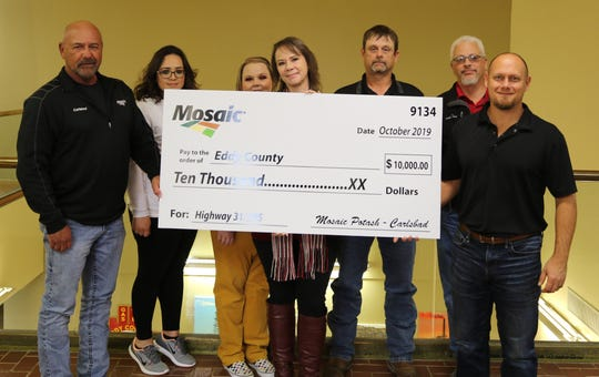 From left: Alan Fernandez, Veronica Parras, Terra Dougan, Jeri Strong, Steve McCroskey, John Anderson and Tonk Chester present a check from Mosaic Potash to Eddy County to help the planning process of the U.S. 285/State Road 31 intersection project.