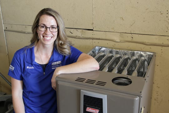 Michelle Robbins of Robbins Heating and Air Conditioning Inc. displays a furnace like the one the company will be donating to a local family in the firm's warehouse in Farmington on Oct. 31, 2019.