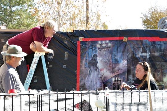 Darrell, James and Shelly Cunningham work on their Cunningham Haunt House before night falls on Oct. 31, 2019 in Farmington.