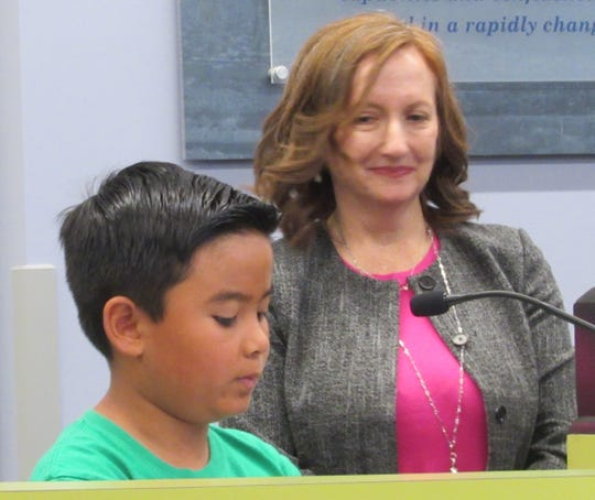 Cahuilla Elementary Third Grader Kenzo Agriam presents the first declaration to the Board of Education as Visual and Performing Arts Coordinator Barbara Anglin watches.