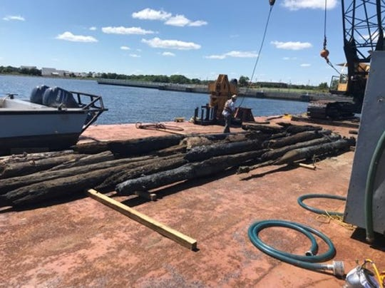 Work crews remove 100-year old piling from water in front of Community Maritime Park.