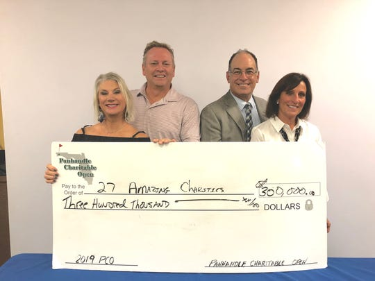 From left, Abbie and Nels Offerdahl and John and Jerre Peacock present a check from the Panhandle Charitable Open to 27 charities during an event on Thursday, Oct. 31, 2019. The open, which honors their late children Ryan Peacock and Ashley Offerdahl, will end after 18 years.