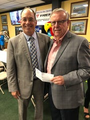 John Clark, executive director of the Council on Aging of West Florida, (right) accepts a check from John Peacock, founder of the Panhandle Charitable Open on Thursday, Oct. 31, 2019. The money raised by the open helps Clark's organization receive matching funds from other entities.