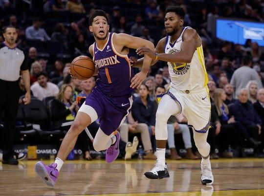 Phoenix Suns' Devin Booker, left, drives the ball past Golden State Warriors' Glenn Robinson III during the second half of an NBA basketball game Wednesday, Oct. 30, 2019, in San Francisco. (AP Photo/Ben Margot)