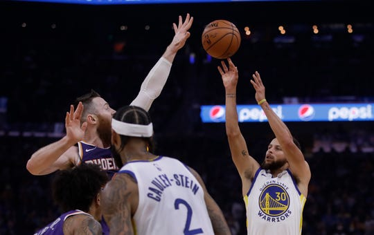 Golden State Warriors' Stephen Curry, right, shoots as Phoenix Suns' Aron Baynes defends during the first half of an NBA basketball game Wednesday, Oct. 30, 2019, in San Francisco. (AP Photo/Ben Margot)