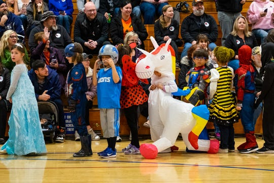 Kids in costumes parade through the gymnasium at Crull Elementary School Thursday, Oct. 31, 2019. The district moved the school's annual parade inside due to the rain.