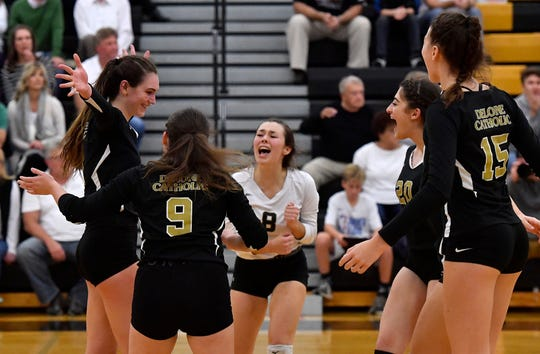 The Delone Catholic Squiretts celebrate after beating York Catholic in the District 3 Class 2-A girls' volleyball semifinal, Thursday, October 31, 2019.