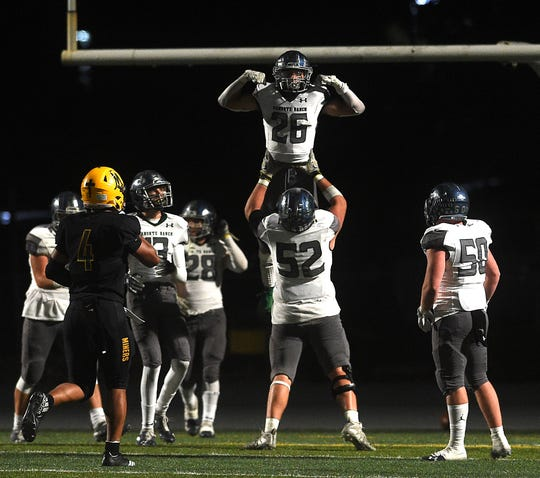 Damonte Ranch's Ashton Hayes (26) gets lifted off the ground by teammate Carter Lewis after he scored a touchdown against Bishop Manogue during their football game in Reno on Oct. 4, 2019.