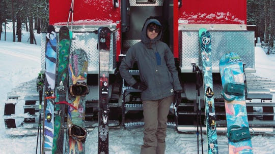 Jennifer Gurecki, CEO of Coalition Snow, poses next to some of the company's skis and snowboards.