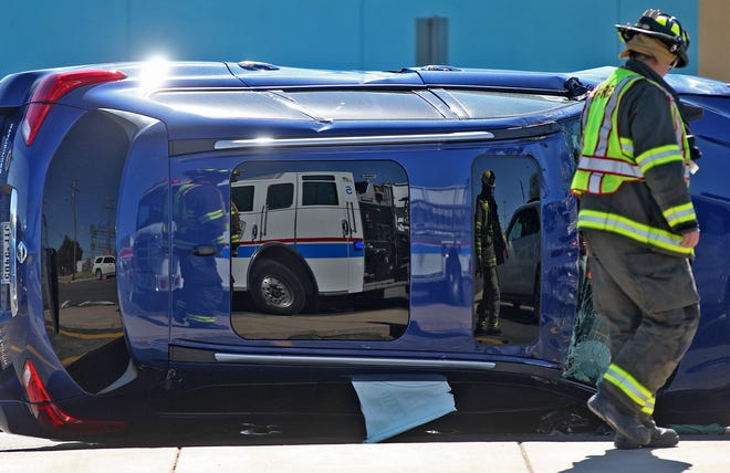 First responders are reflected in the sun roof of an overturned SUV at the scene of a three vehicle crash near HEB on Avenue N on Thursday, Oct. 31, 2019. No injuries were reported at the scene.
