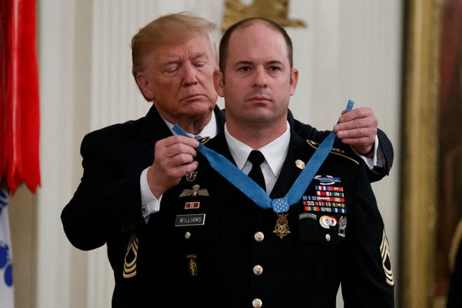 President Donald Trump places the Medal of Honor on Army Master Sgt. Matthew Williams, currently assigned to the 3rd Special Forces Group, during a Medal of Honor Ceremony in the East Room of the White House, Wednesday, Oct. 30, 2019, in Washington.