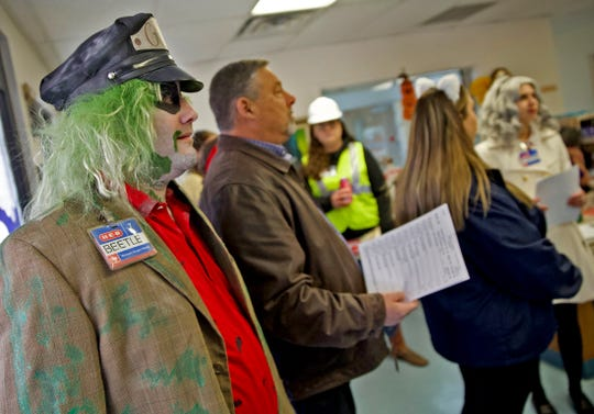 Victor Candelario, dressed as the character Beetlejuice at far left, gets ready to deliver food at the Meals for the Elderly facility in San Angelo with other H-E-B employees Thursday, Oct. 31, 2019.