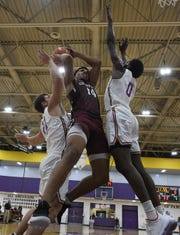 Centenary's Ty Prince gets sandwiched by LSUS's Landon Powell and Gilbert Thomas during Wednesday's game at The Dock.