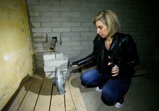 Charity Reeb turns the crank on a hand pump that would draw fresh air into a bomb shelter believed to have been built in the late 1950s or early 1960s in the basement of a house at 1235 E. Walnut St. in Springfield, Mo.