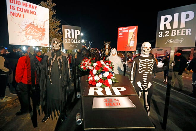 A ghoulish group of pallbearers stand in front of a casket representing 3.2% beer, Wednesday, Oct. 30, 2019, in Salt Lake City. After 86 years, this Halloween marks the last day 3.2% beer will be sold in Utah stores. Beginning Nov. 1, Utah stores will be selling up to 5% ABV beer, and Budweiser wants to celebrate with a funeral complete with their famous Clydesdales, in the background. (AP Photo/Rick Bowmer)