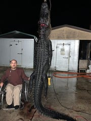 Thad Isenhour, of Port St. Lucie, Fla., is pictured just before 1 a.m. Thursday, Oct. 24, 2019, with the 11-foot-10 alligator he'd caught hours before on Blue Cypress Lake in Indian River County.