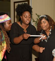 "Dee Coe, left, Adrienne Huggins and Ashley Gilbert find clues at the END It! Mystery Dinner Theater fundraiser ""The Last Groove Goes Platinum."""
