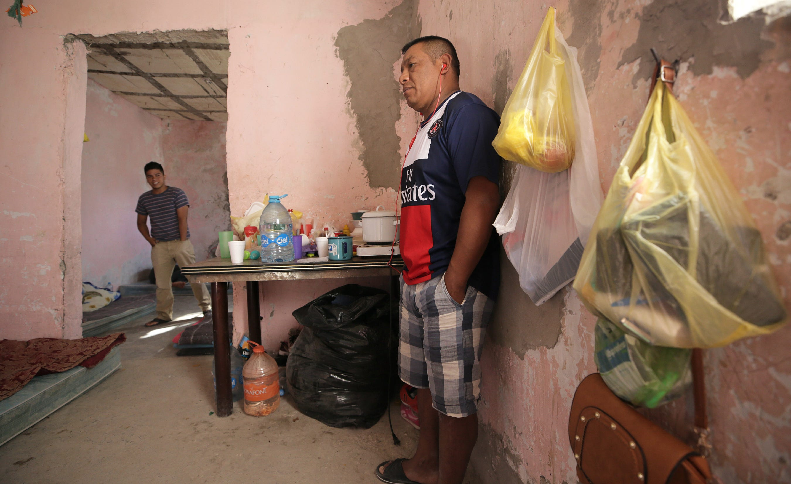Francisco Sical, right, found shelter with his 10-year-old daughter in summer 2019 in a half-finished house in Juárez. A dozen migrants from his native Guatemala, as well as Honduras and El Salvador, waited on court hearings in the USA under the Trump administration's Migrant Protection Protocols.