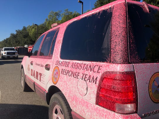 A vehicle is covered Thursday by red fire retardant from efforts to battle the Easy Fire in Simi Valley and Moorpark. After a tough day battling the flames Wednesday, the situation was calmer Thursday.