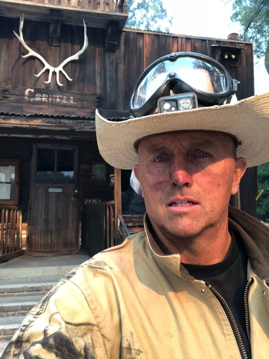 Morgan Runyon, owner of The Old Place in Cornell near Agoura Hills, snaps a selfie in front of the restaurant while fighting the Woolsey Fire in November 2018.