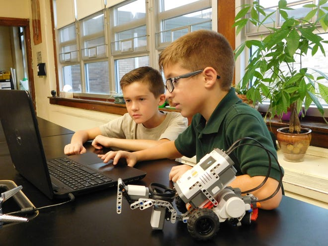 Marco Cervini (left), a fifth-grader, and Anthony Leo, a fourth-grader, work on programing their robot with a touch sensor similar to that used by robotic vacuums during Lego Robotics, an after school club at Edgarton Christian Academy in Newfield.