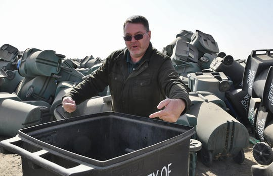 Public Works Manager Jim Ross explains why some split recycle cans can't be retrofitted with single lids. Behind him, roughly 30,000 cans await their fate in a 5-acre lot beside the city's wastewater treatment plant on Oct. 30, 2019.