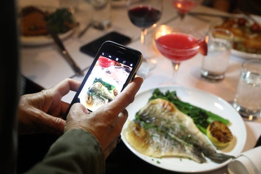"Lohud food reporter Jeanne Muchnick takes a photo of her branzino served with lemon, fresh herbs and broccolini during ""Dinner with Jeanne"" at Granita in Hartsdale Oct. 30, 2019."