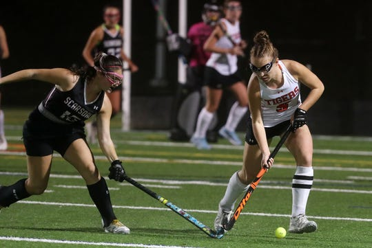 From right, Mamaroneck's Sophie Showers (5) moves the ball away from Scarsdale's Mackenzie Mauro (15) during field hockey playoff action at Mamaroneck High School Oct. 30, 2019. Mamaroneck won the game 2-0.