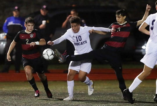 Rye's Malcolm McQueeney (3) kicks the ball away from Byram Hill Yusuf Hafez (10)  during the Section 1 Class A semifinal at Rye High School Oct. 30, 2019. Rye won the game 4-2.