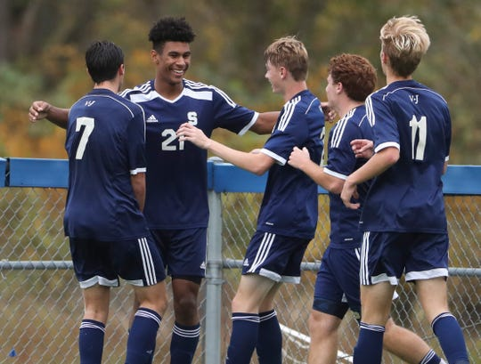 Salesianum players surround Ethan Hinds (21) after his second goal against Archmere on Wednesday. The Sals won 3-1.