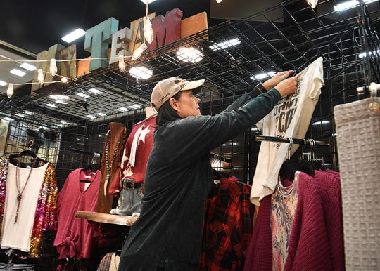 Bonnie Dillon, owner of My Team Boutique, hangs up women's clothing items at her Christmas Magic booth Thursday.at the Ray Clymer Exhibit Hall. She also sells unique handmade jewelry.