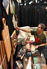 Tessa Schafer of Board Stiff Design sets up a display of custom wood products as she prepares for Christmas Magic 2019 Thursday at the Ray Clymer Exhibit Hall. Schafer and her husband, Nathan, make high-end cutting boards, serving trays and tables.