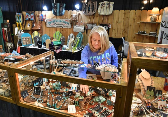 Dawn McCulloch of Dee's Collections arranges silver and turquois jewelry at her booth as she prepares for Christmas Magic 2019.