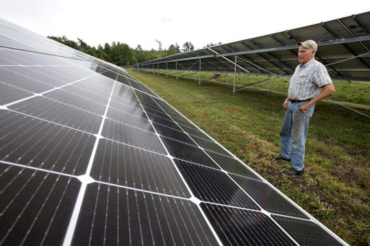 In this Wednesday, Oct. 2, 2019 photo cranberry grower Dick Ward, of Carver, Mass., stands near a solar array in a cranberry bog on his farm, in Carver. Plummeting cranberry prices has America's cranberry industry eyeing a possible new savior: solar power.
