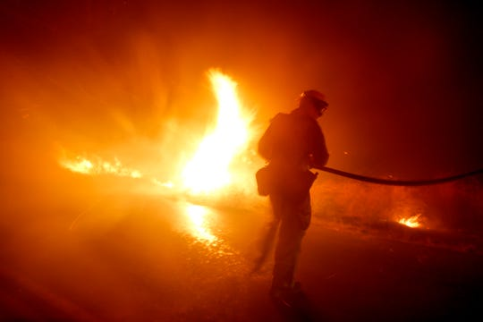 A firefighter battles a wildfire in Riverside, Calif. Thursday, Oct. 31, 2019.