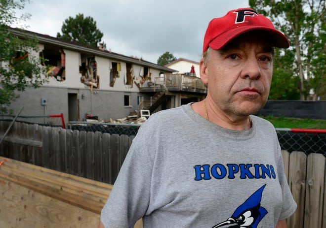 In this June 5, 2015, photo, Leo Lech stands on a pile of wood in his neighbor's yard that overlooks the back of his home in Greenwood Village, Colorado. A federal appeals court says police don't have to pay for the damage done to a suburban Denver home they rendered uninhabitable during a 19-hour standoff with an armed robbery suspect.