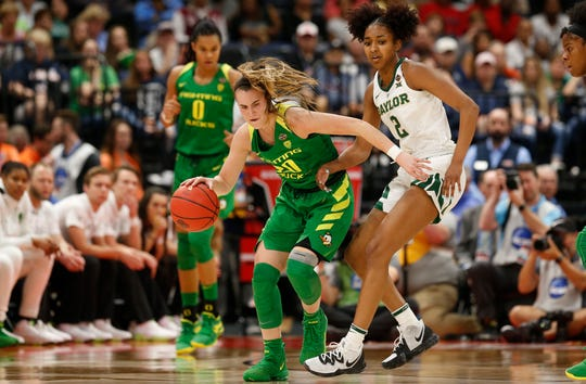 Oregon guard Sabrina Ionescu dribbles the ball as Baylor guard DiDi Richards  defends her during the Final Four of the 2019 NCAA tournament.