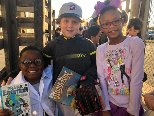 """Traivean Hunter, left, dressed as Frank Einstein, paraded throughout Taylor Elementary on Friday with classmates Bryson Burch (Babe Ruth) and X'Riyah White (Nila, from """"Shimmer and Shine: Magical Mermaids""""). The second-grade students made their way through most of the classrooms, showing off their favorite stories and characters."""