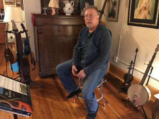 Joe Penland sits beside his instruments inside his Ramsey Building apartment. The space sits inside a 1916 structure, a former hardware store, that he helped renovate.