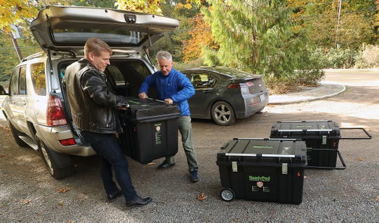 Fred Bruner, left, and Scott James remove the ReadyPod Shelter-In-Place Kit from their vehicles at Bainbridge Island's Centennial Park on Thursday.