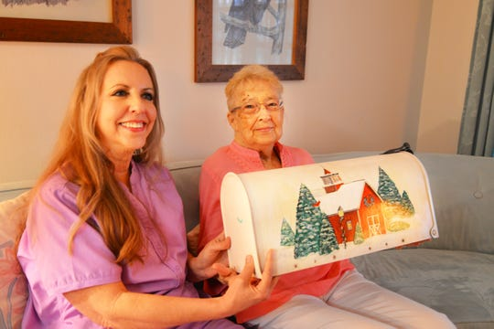 Sylvia Knight visits with registered nurse Liz Walther, who's with Hospice of St. Francis, as they look at the Christmas mailbox Sylvia painted.  Knight lost her husband, former police officer Dick Knight, in July 2018. He, too, was in hospice care.