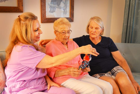 "Hospice patient Sylvia Knight, center, shows her ""angels"" -- hospice nurse Liz Walther and Knight's neighbor, Linda Allen -- one of the clothespin dolls she made."
