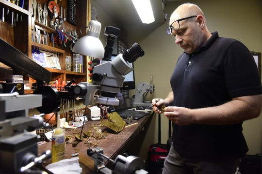 Steve Shroyer examines a gear from a clock at his workbench inside Cottage Clock Shop in Galion.