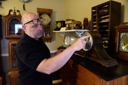 Steve Shroyer changes the time on a time-and-strike winding clock inside his business, Cottage Clock Shop, in Galion.