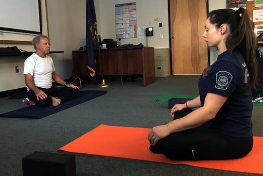 Jim Dunn, of the Vermont Center for Responder Wellness, left, leads a group of South Burlington firefighters in a mindfulness and breathing exercise at the fire department on Tuesday, October 29, 2019.