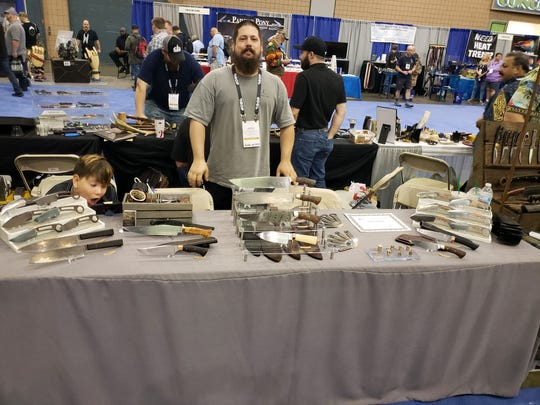 Justin Chenault showing off his knives at a show