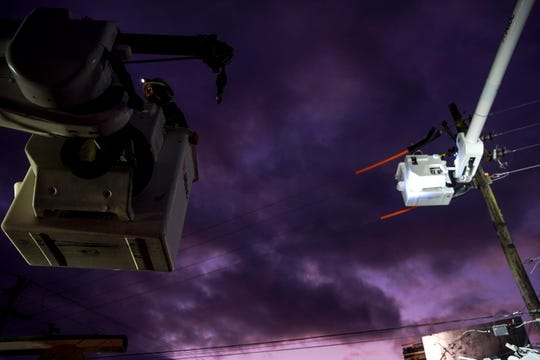 Travis Rigsby is raised in a second crane to join Brian Quick at the top of a telephone pole to work to restore power along Providence Boulevard near Cave Street in Clarksville, Tenn., on Thursday, Oct. 31, 2019.