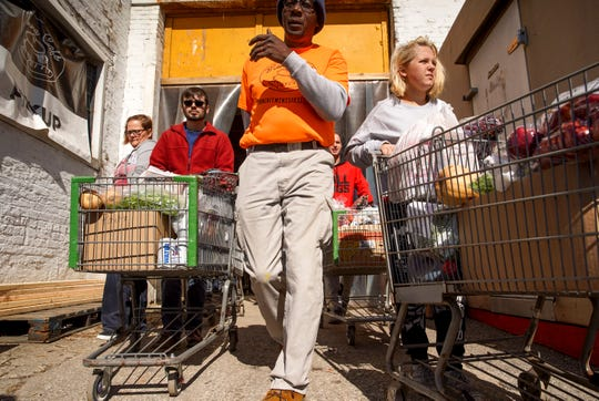Volunteers get into two file lines with carts of food for distribution to those that lose food in the aftermath of the storm at Manna Cafe Village in Clarksville, Tenn., on Friday, Nov. 1, 2019.