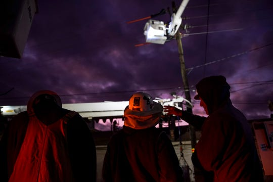 Linemen from Huntsville, Alabama watch over operations as a second basket is prepared for a worker to be brought up and help work to restore power along Providence Blvd near Cave Street in Clarksville, Tenn., on Thursday, Oct. 31, 2019.