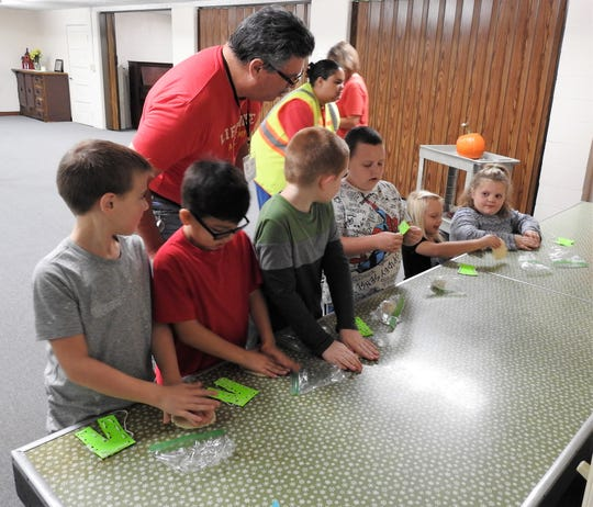 Pastor Larry Massie oversee second-graders Blake Newell, Desean Cruze, Noah Napier, Kaiden George, Daisy Hawthorne and Zoey Mounts as they work clay as Adam worked the ground to produce food in the Bible. Students of Conesville Elementary School participate in the release time program with parental permission.